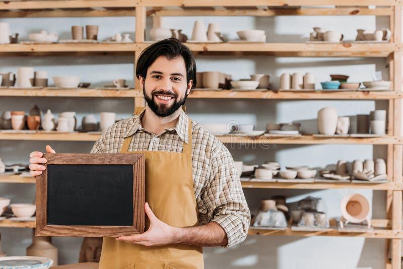 dueño barbudo masculino con la pizarra en taller de la cerámica imagen de archivo
