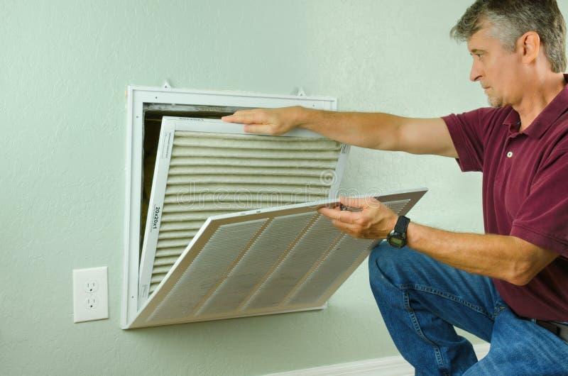Dueño casero que substituye el filtro de aire en el acondicionador de aire fotografía de archivo libre de regalías
