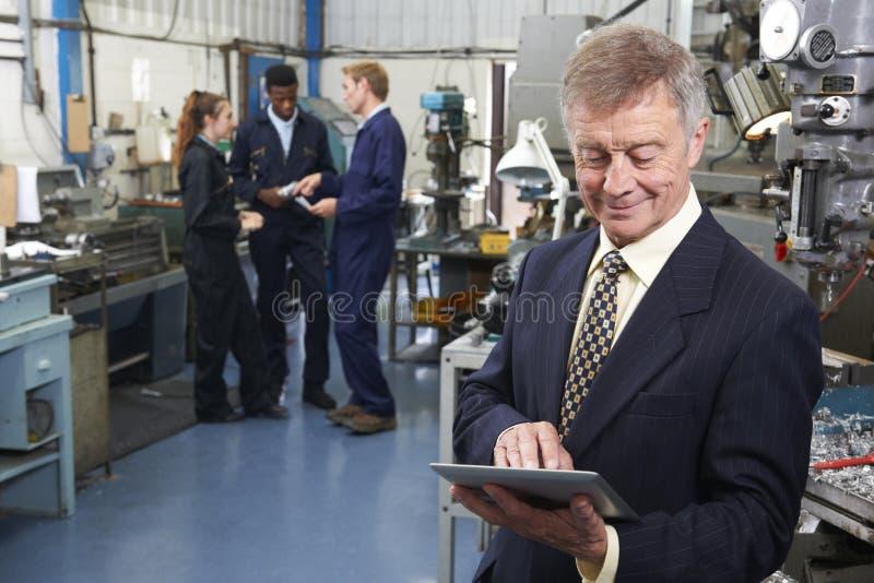 Dueño de la fábrica de ingeniería usando la tableta de Digitaces con el personal adentro imágenes de archivo libres de regalías