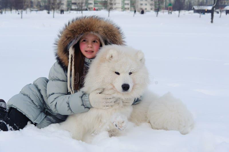 Dueño de la mujer que abraza el perro blanco del samoyedo fotos de archivo