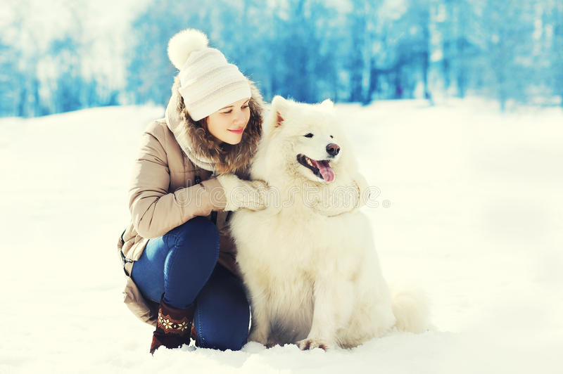 Dueño de la mujer que abraza el perro blanco del samoyedo en invierno foto de archivo