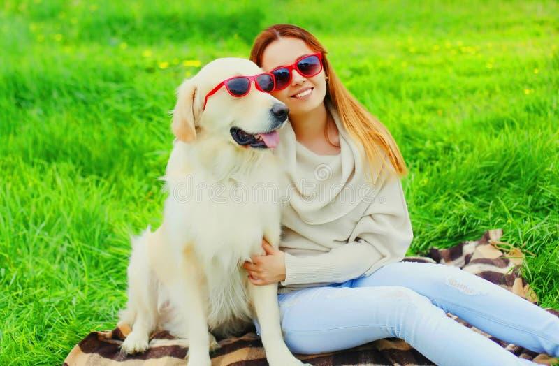 Dueño de la mujer y perro sonrientes felices del golden retriever en gafas de sol junto en hierba en verano imagenes de archivo