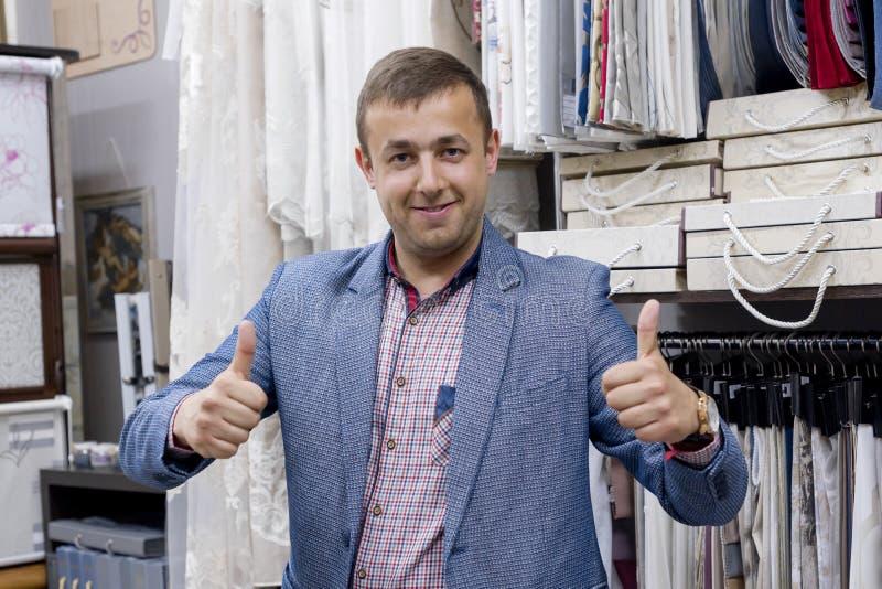 Dueño de tienda positivo confiado joven de la tela del hombre de negocios que muestra los pulgares para arriba, autorización de imagen de archivo libre de regalías