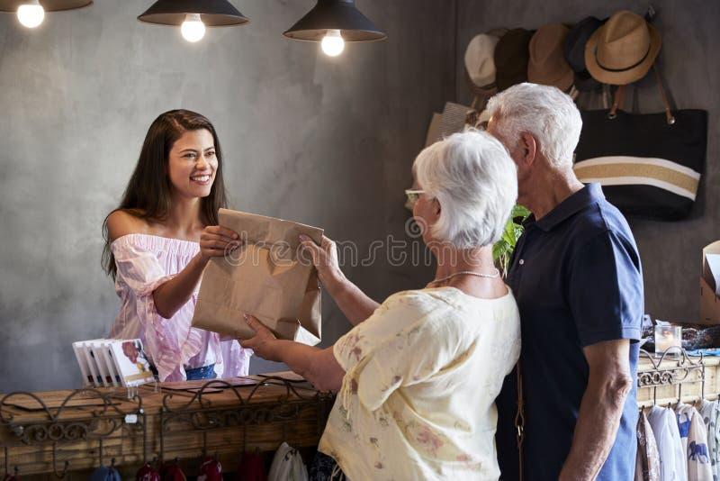 Dueño de tienda que se coloca detrás del escritorio de efectivo que sirve a clientes mayores imagen de archivo libre de regalías