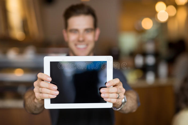 Dueño del café que muestra la tableta de Digitaces imagenes de archivo