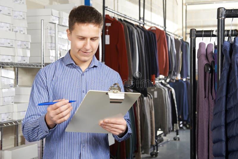 Dueño del comienzo del negocio de moda para arriba en Warehouse con el tablero imágenes de archivo libres de regalías