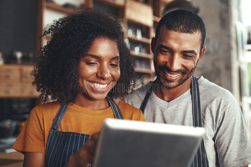 Dueño sonriente del café en el delantal que mira la tableta digital fotografía de archivo