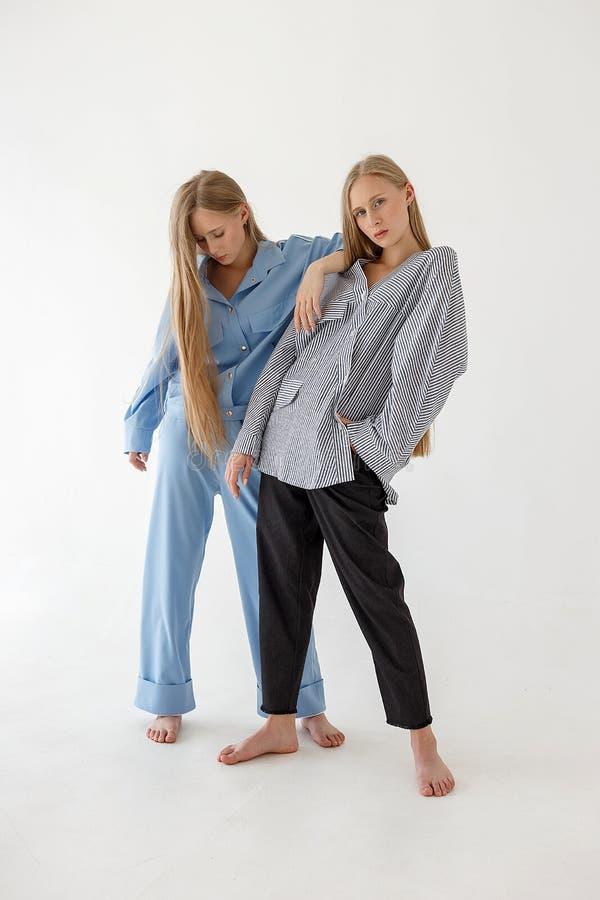 Due abbastanza giovani sorelle gemellate con capelli biondi lunghi che posano sul fondo bianco in vestiti di grande misura Photos fotografia stock libera da diritti