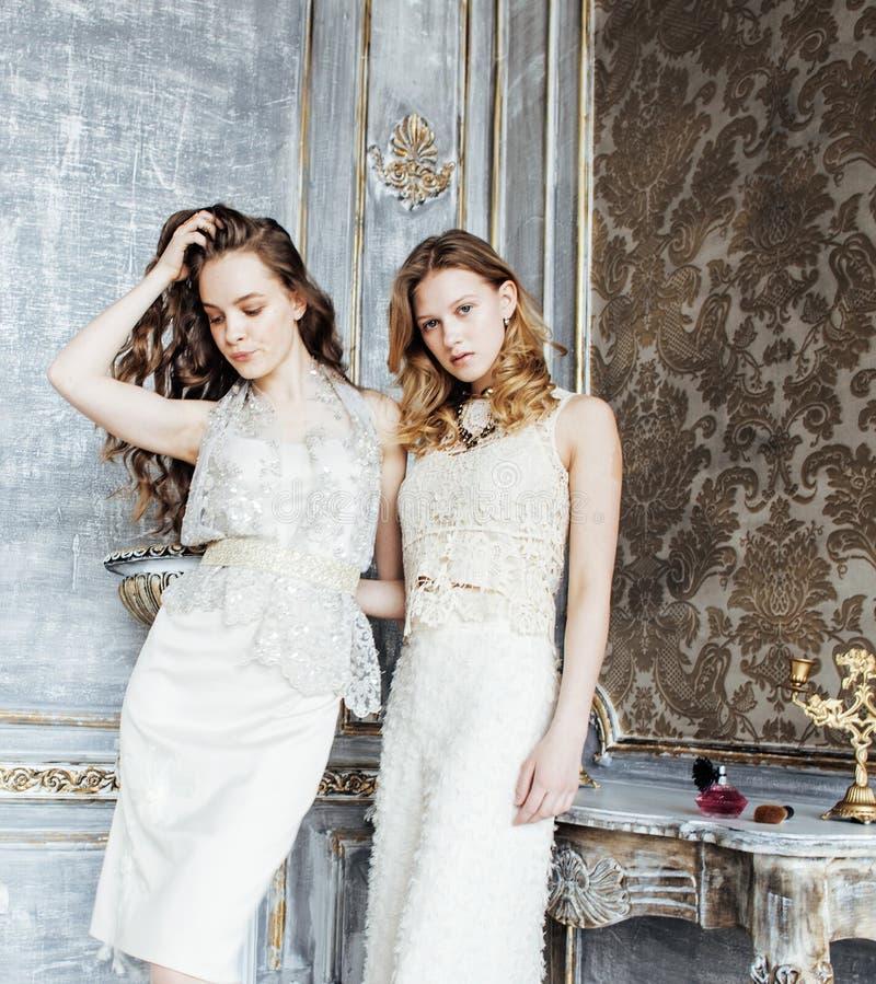 Due acconciature ricce bionde delle sorelle gemellate graziose nell'interno di lusso della casa insieme, concetto ricco dei giova fotografie stock libere da diritti