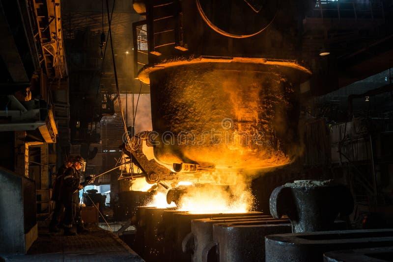 Due addetti alla lavorazione dell'acciaio cola il metallo liquido negli stampi dal carro armato fotografia stock libera da diritti