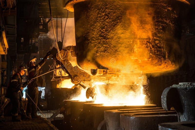 Due addetti alla lavorazione dell'acciaio cola il metallo liquido negli stampi dal carro armato immagine stock