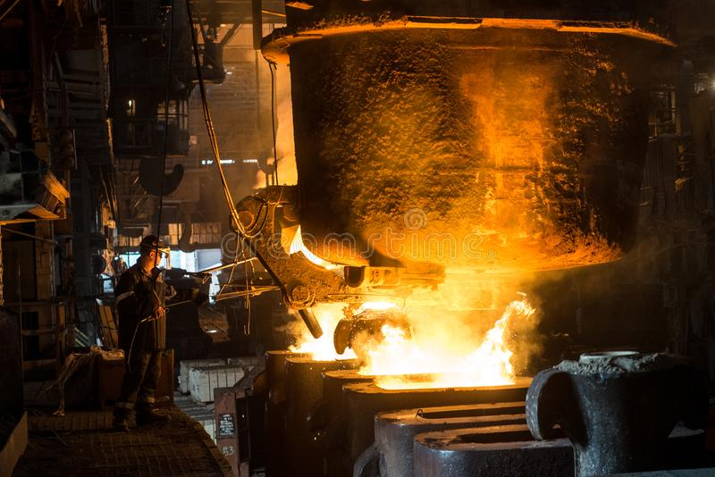 Due addetti alla lavorazione dell'acciaio cola il metallo liquido negli stampi dal carro armato immagini stock