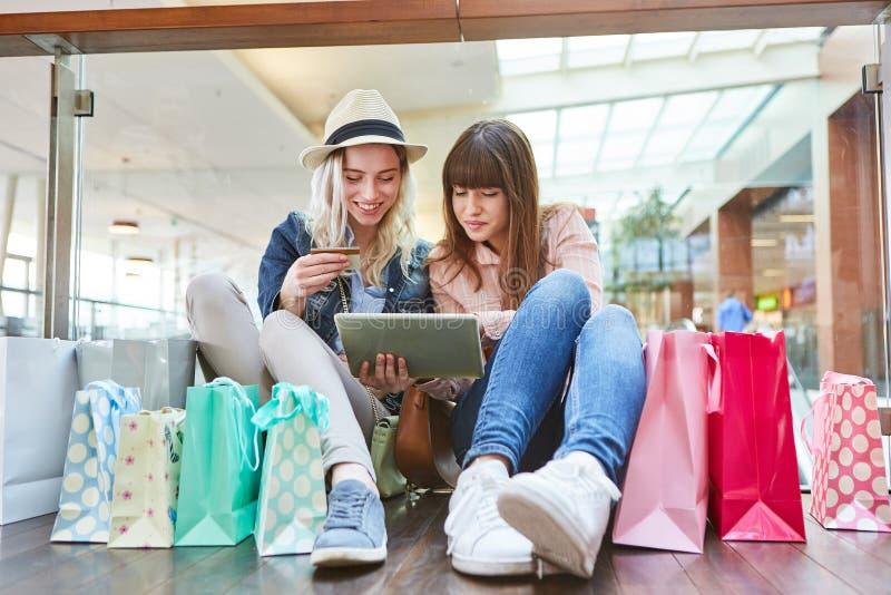 Due adolescenti che comperano online immagine stock libera da diritti
