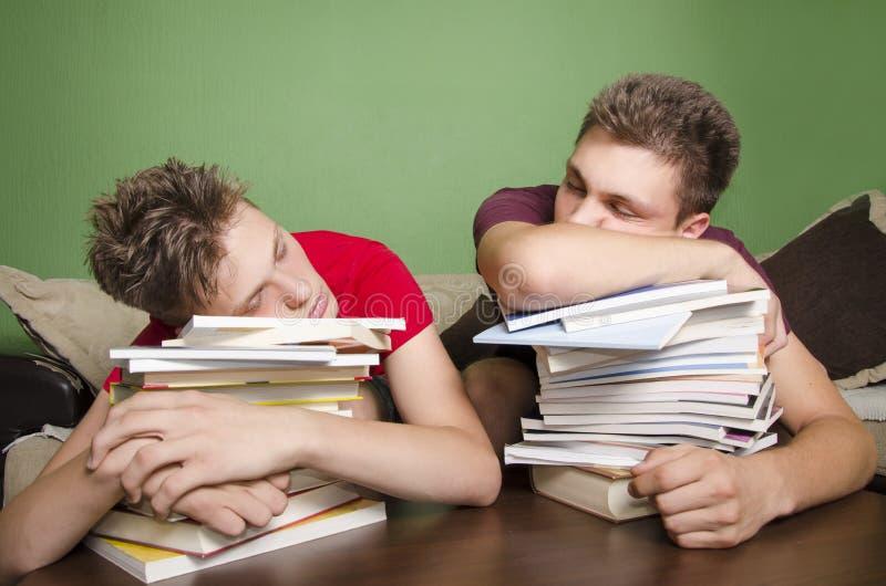 Due adolescenti che dormono sui libri fotografia stock