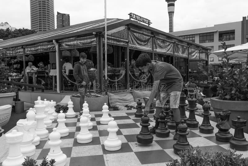 Due adolescenti che giocano scacchi all'aperto immagini stock
