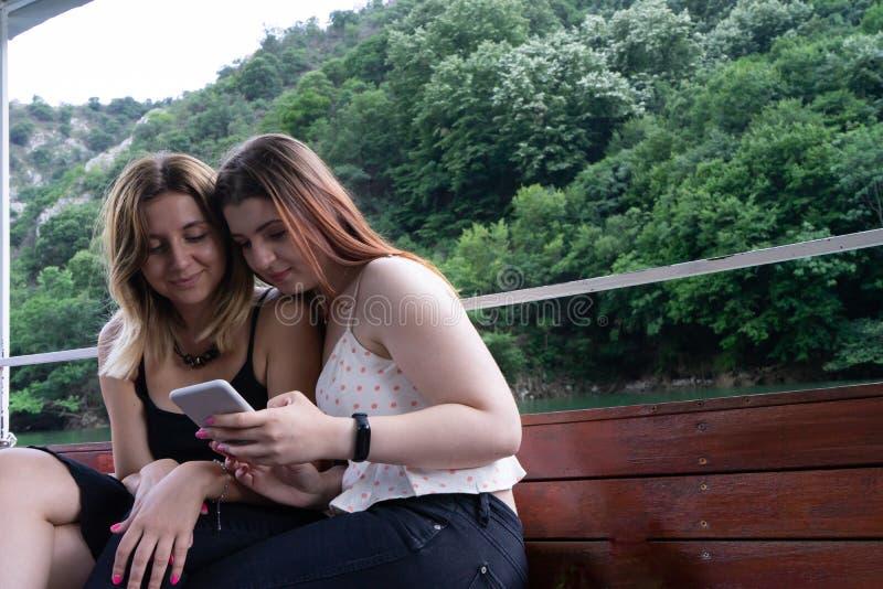 Due adolescenti che guardano un video in un telefono cellulare e ridere, sedentesi in una barca Amici di ragazze caucasici dedica immagini stock