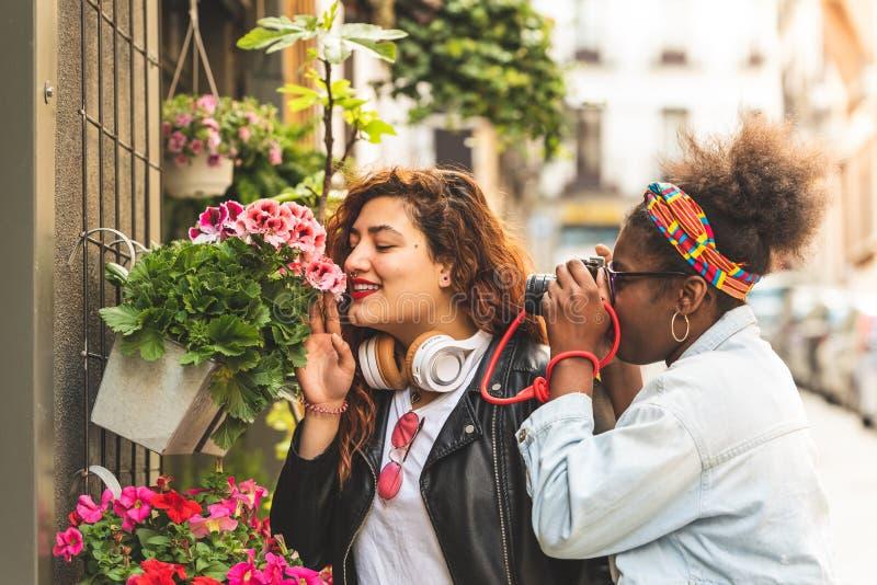 Due adolescenti che odorano i fiori fotografie stock