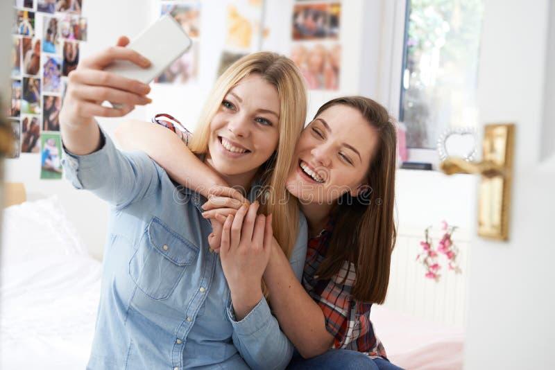 Due adolescenti che prendono Selfie in camera da letto a casa fotografia stock