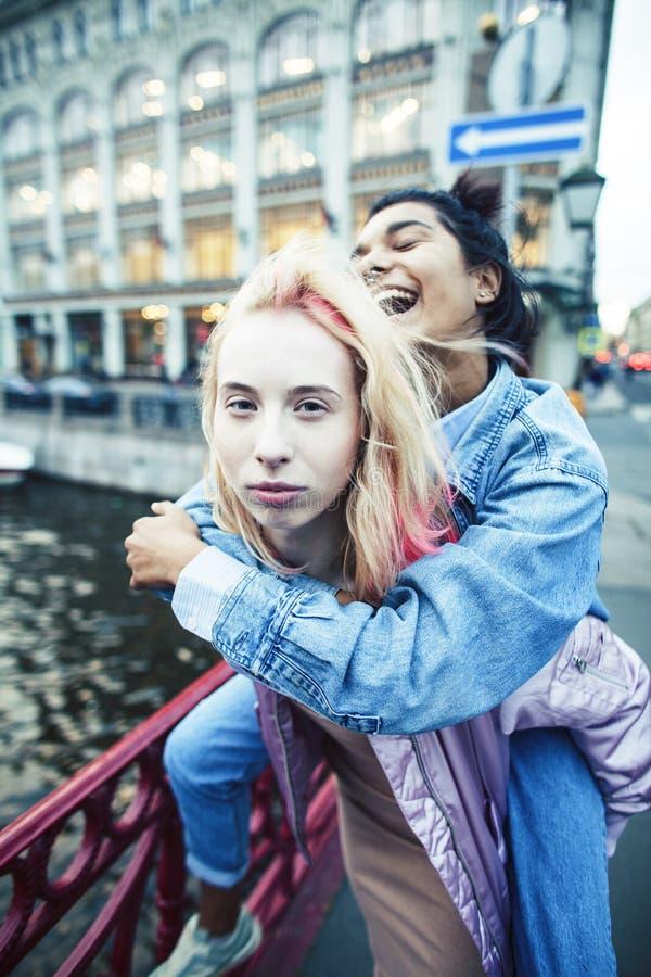 Due adolescenti davanti alla costruzione dell'universit? che sorridono, divertendosi, fine reale di concetto della gente di stile immagini stock libere da diritti