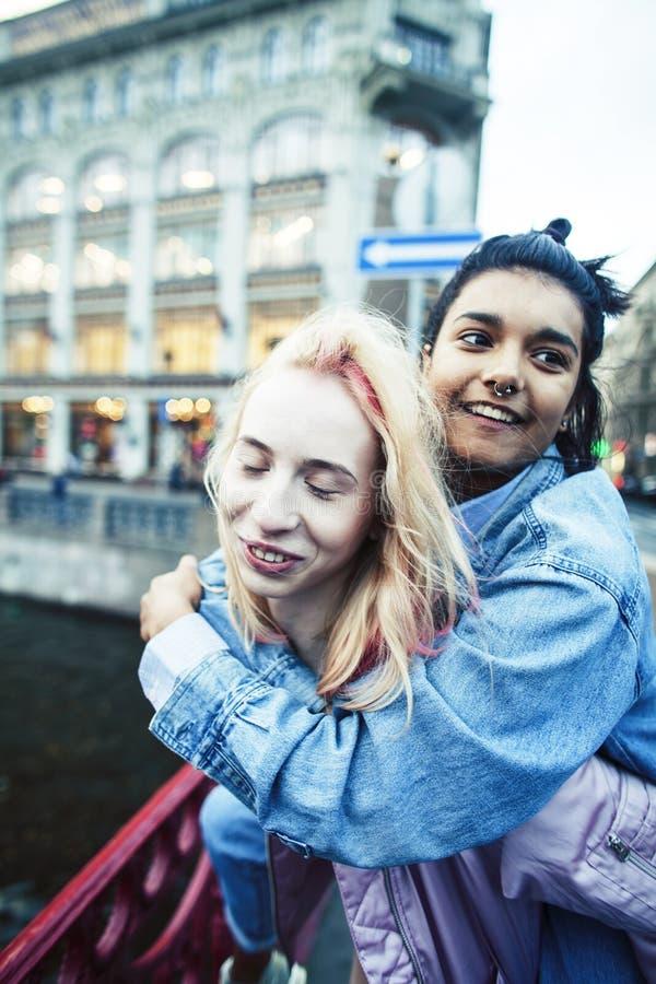 Due adolescenti davanti alla costruzione dell'universit? che sorridono, divertendosi, fine reale di concetto della gente di stile immagine stock