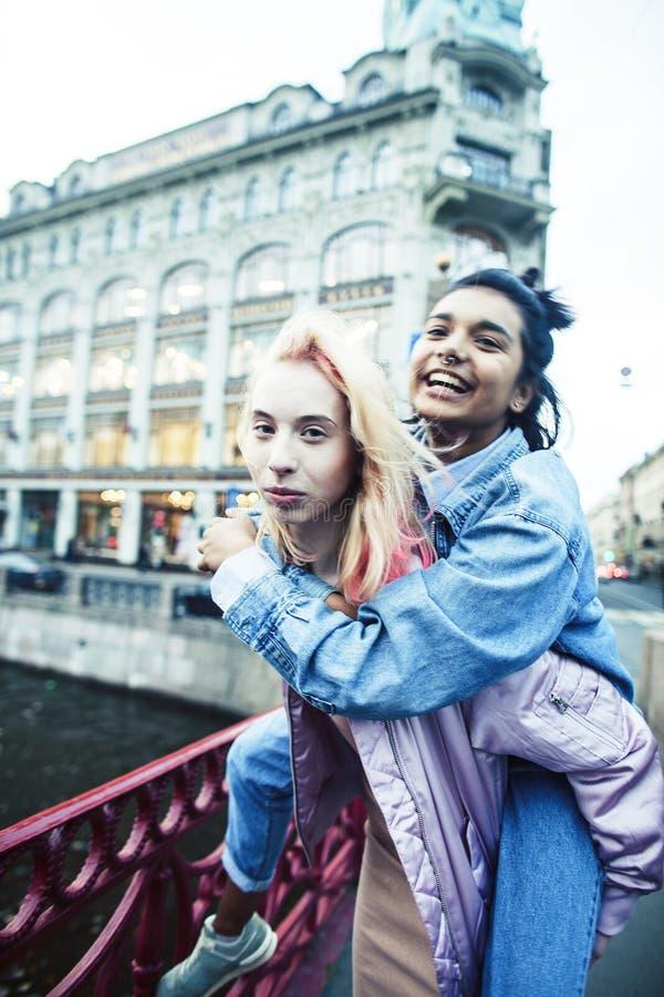 Due adolescenti davanti alla costruzione dell'universit? che sorridono, divertendosi, fine reale di concetto della gente di stile fotografia stock libera da diritti