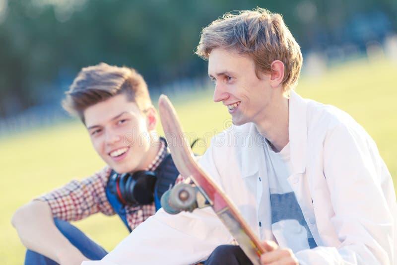 Due adolescenti di buon umore con un pattino immagine stock