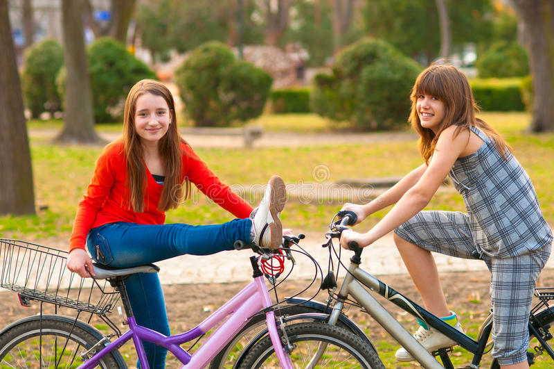 Due adolescenti graziosi che hanno divertimento sulle biciclette fotografia stock libera da diritti