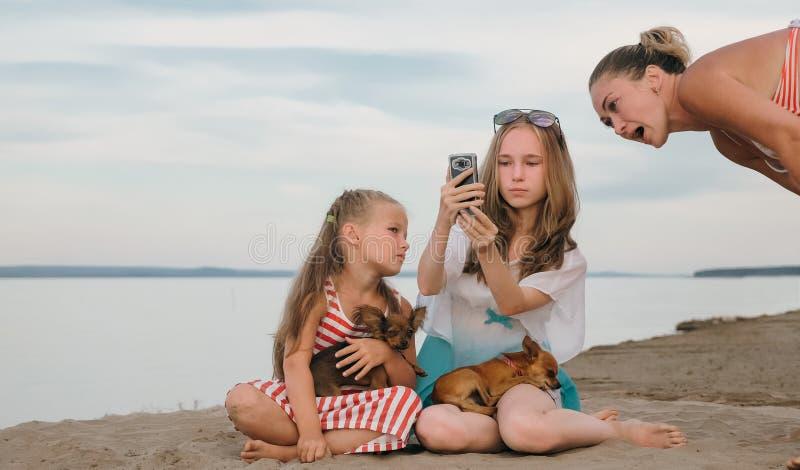 Due adolescenti stanno sedendo su una spiaggia sabbiosa, su Internet in telefono immagine stock