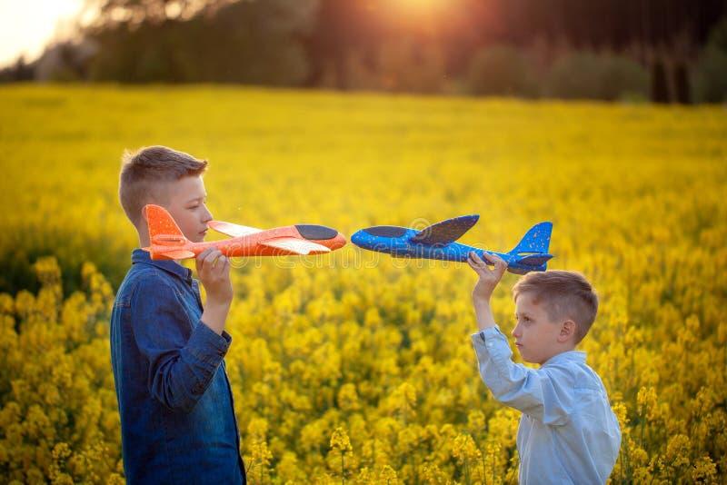 Due aeroplani dei giocattoli nei ragazzi delle mani che se esaminano nel campo giallo il giorno di estate immagini stock libere da diritti