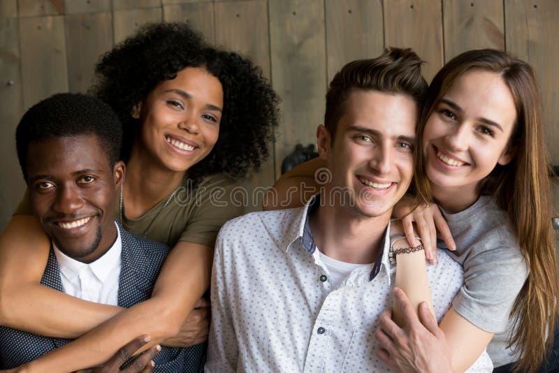 Due africani e coppie caucasiche che abbracciano esaminando macchina fotografica, p fotografia stock