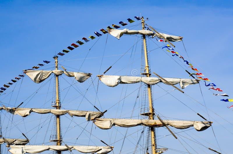 Due alberi con le vele acciambellate e le bandiere contro una s blu fotografia stock libera da diritti