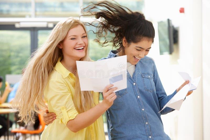 Due allievi adolescenti che celebrano riuscito risultato dell'esame fotografia stock