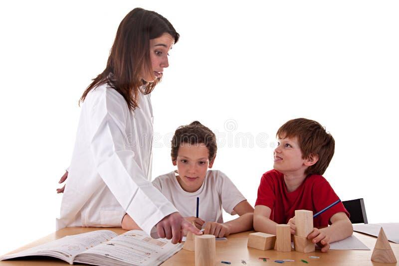 Due allievi con l'insegnante fotografia stock