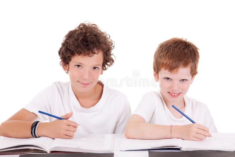 Due allievi con una matita, scrivente fotografia stock libera da diritti