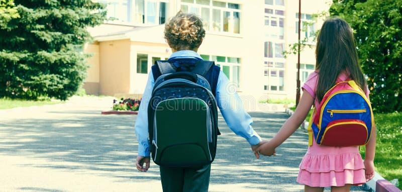 Due allievi della scuola primaria vanno di pari passo Ragazzo e ragazza con le borse di scuola dietro la parte posteriore Due all fotografia stock