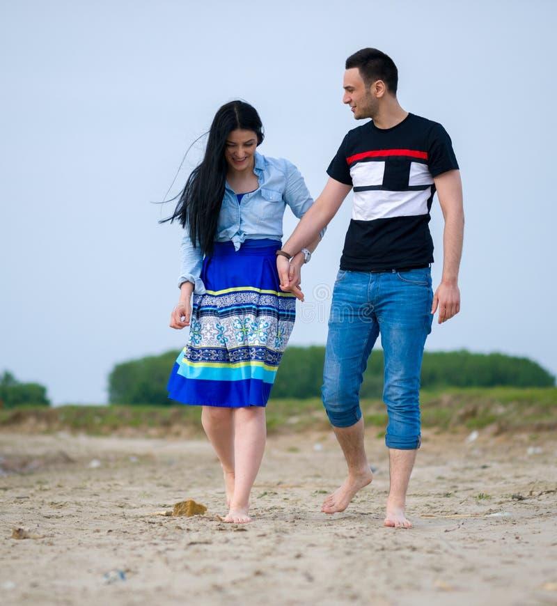 Due amanti che si tengono per mano e che camminano sulla spiaggia fotografia stock libera da diritti