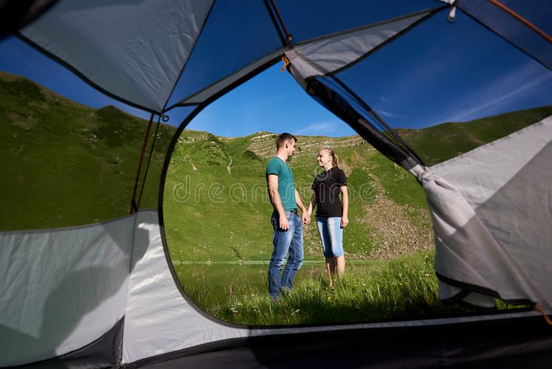 Due amanti sulla vacanza in montagne stanno tenendo per mano contro fondo di bello paesaggio fotografia stock libera da diritti