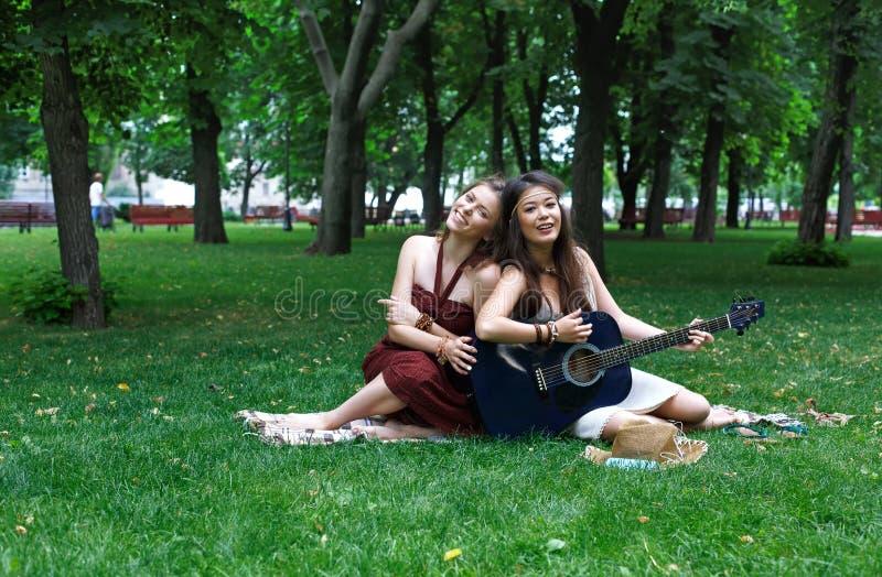 Due amiche alla moda eleganti di boho felice con la chitarra, picnic fotografia stock