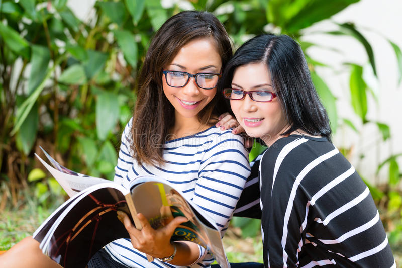 Due amiche asiatiche che leggono rivista immagini stock