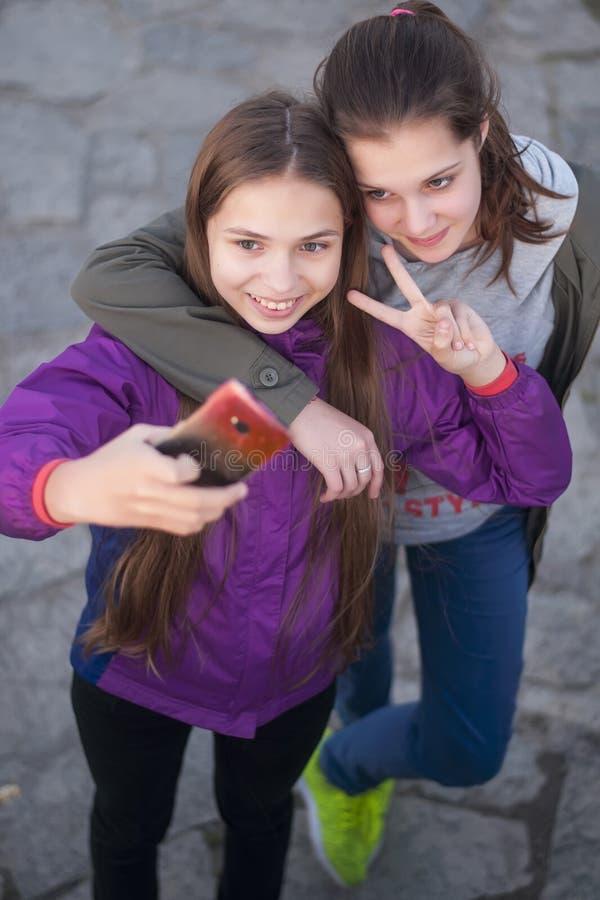 Due amiche attraenti che prendono autoritratto con la loro macchina fotografica del telefono all'aperto fotografie stock