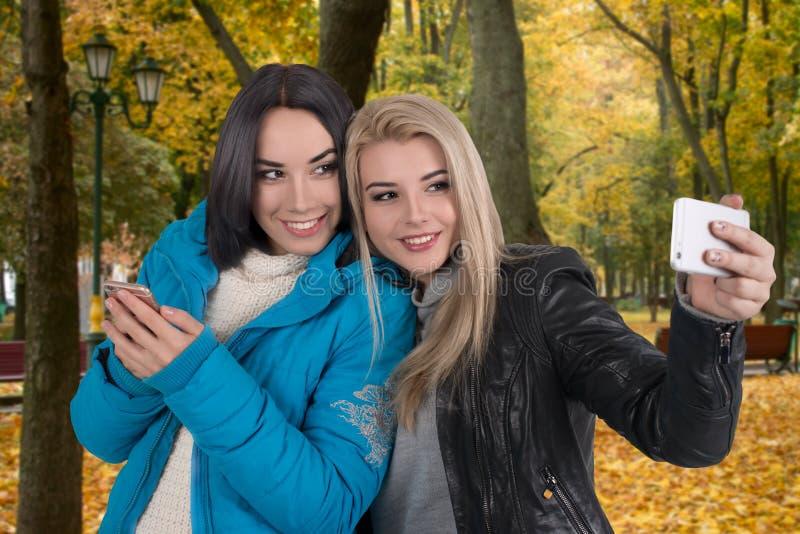 Due amiche camminano nel parco di autunno e prendono il selfie in telefono fotografie stock libere da diritti