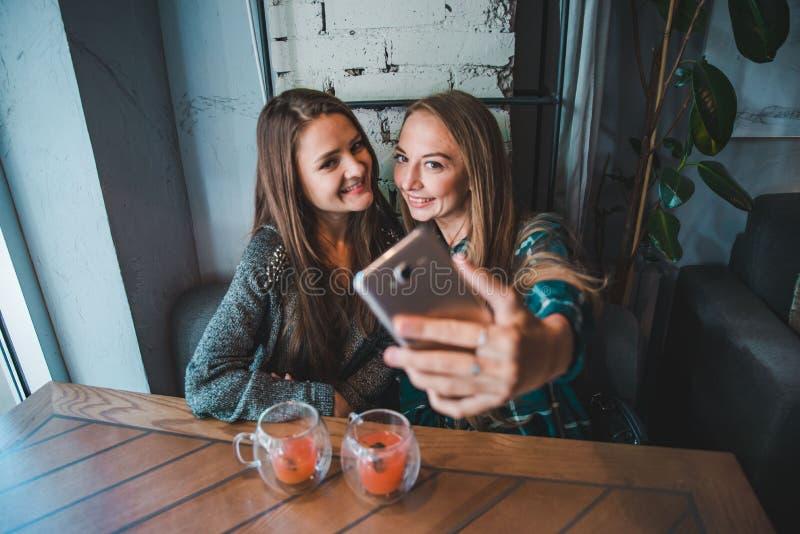 Due amiche che prendono selfie mentre sedendosi in caffè immagini stock