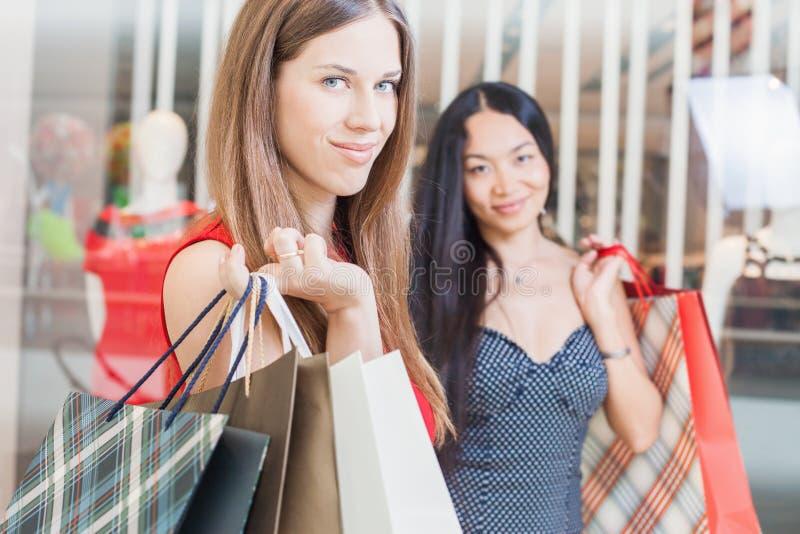 Due amiche di modo che comperano al centro commerciale fotografia stock libera da diritti