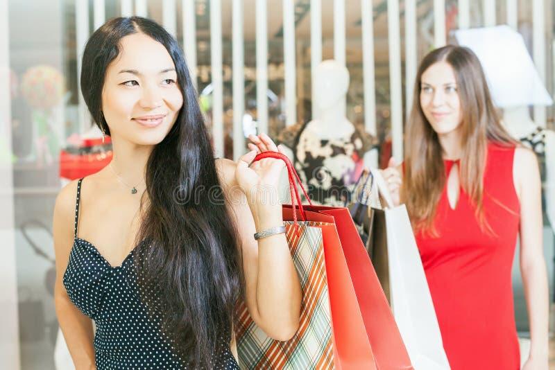 Due amiche di modo che comperano al centro commerciale immagini stock