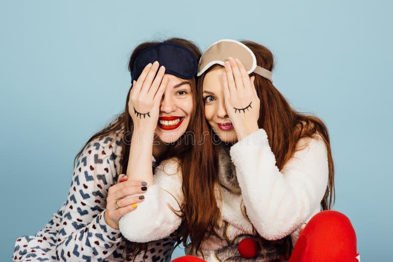 Due amiche di risata in pigiami e con una maschera di sonno chiudere l'un l'altro i loro occhi immagini stock