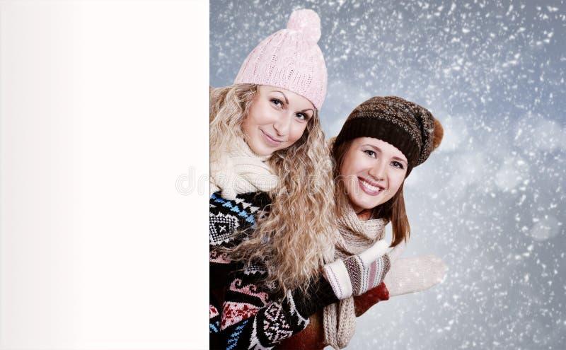 Due amiche dietro un bordo bianco immagine stock libera da diritti