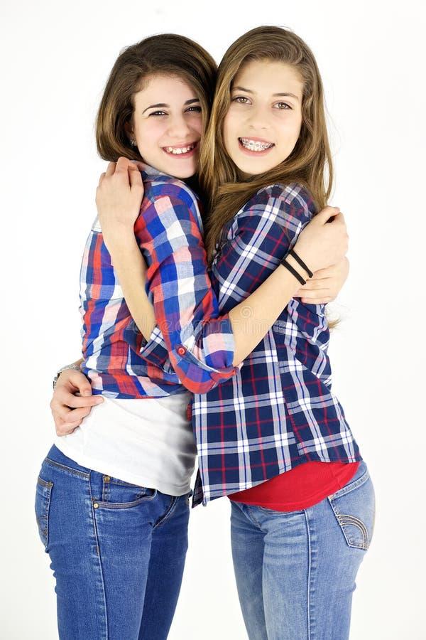 Due amiche felici che abbracciano nello studio fotografia stock