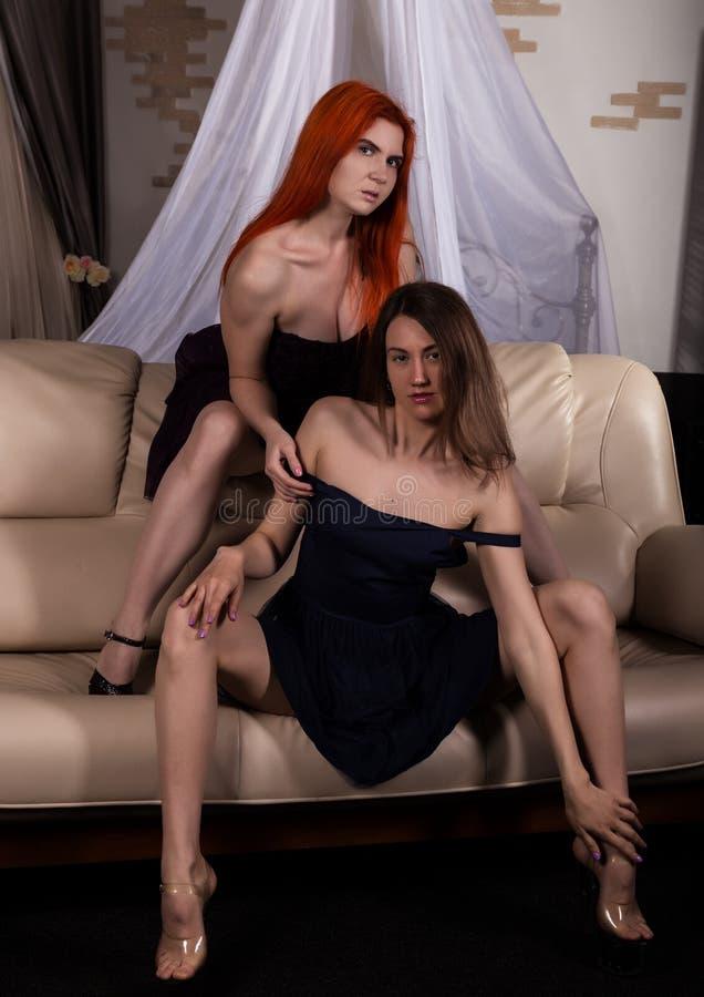 Due amiche lesbiche attraenti divertendosi su un sofà nella camera di albergo le lesbiche godono di di datare fotografia stock