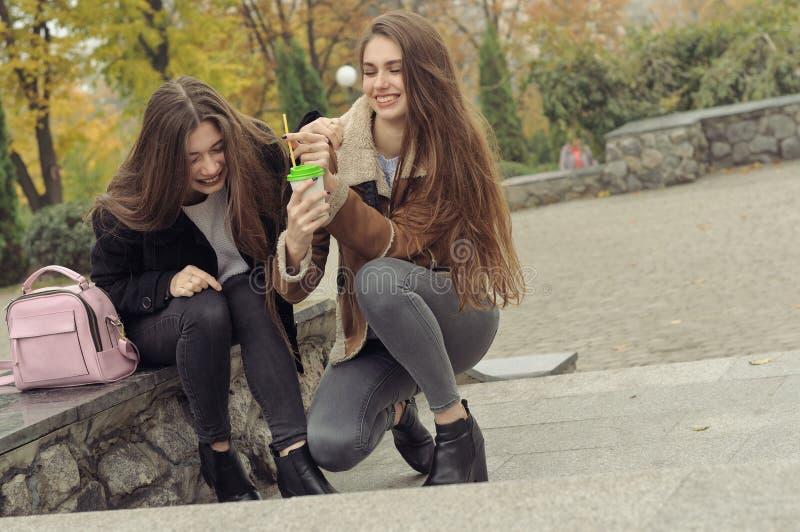 Due amiche provano a scaldarsi con una bevanda calda nell'aria aperta fotografia stock