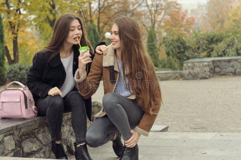 Due amiche provano a scaldarsi con una bevanda calda nell'aria aperta immagine stock